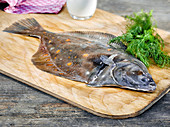 A flounder on a wooden board