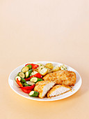 Breaded chicken steaks with potatoes, zucchini and peppers
