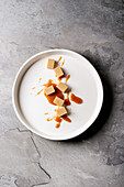Salted caramel fudge candy with caramel sauce in white plate over grey texture background