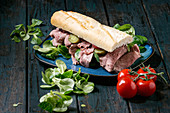 Beef and vegetables sandwich with sliced meat, pickled cucumber, green salad in blue ceramic plate