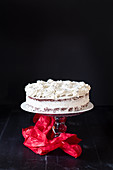 A creamy cake on a cake stand against a black background