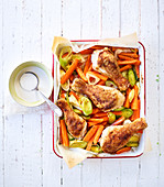 Chicken legs, carrots and leek on a baking tray