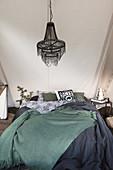 Bett mit dunklen Decken, darüber Kronleuchter im Zelt