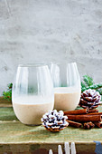 Glasses of Traditional winter eggnog with milk, rum and cinnamon, christmas decorations on wooden table