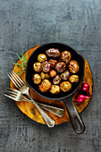Tasty fried baby potatoes in vintage cast iron pan on wooden board over black concrete background