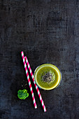 Glass filled with fresh green smoothie on dark concrete table