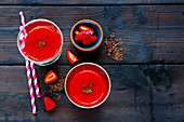 Glass jars of fresh red smoothie with strawberry and chocolate on old wooden background