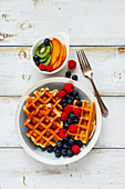 Delicious breakfast set. Warm homemade traditional belgian waffles with fresh berry and fruit on white rustic wooden background