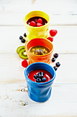 Delicious colorful smoothies jars with berries and fruits on white wooden board