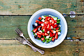 Healthy summer watermelon feta salad with arugula and fresh strawberry on wooden background