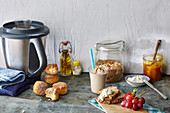 A still life with bread rolls, a smoothie, cereals, bread, spreads, fruit, and food processor