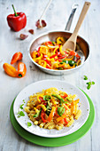 Spiral pasta with colourful pepper strips and basil