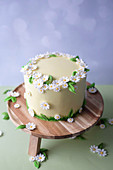 A spring cake with a buttercream filling decorated with daisies