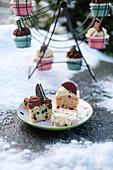 Verschiedene Cupcakes auf Teller und Cupcake-Ständer im Schnee