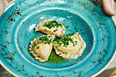 Kärntner Kasnudeln (Austrian ravioli filled with quark and potatoes) with chives on a plate