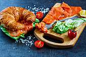 A croissant with smoked salmon and lettuce leaves