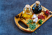 Vinegar, oil, herbs and spices on a vintage wooden board