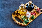 Essig, Öl, Kräuter und Gewürze auf Vintage-Holzbrett