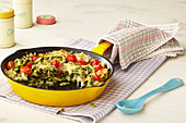 Gratinated spinach egg noodles with tomatoes in a pan