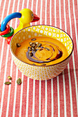 Pumpkin soup with oil and seeds in a bowl next to a baby rattle