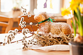 Easter lamb cake on a straw nest, decorated with pussy willow branches