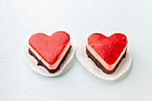 Two heart-shaped strawberry cream tarts on a white background