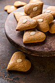 Gingerbread hearts with flaked almond on a wooden plate