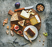 Flat-lay of cheese platter with cheese assortment, figs, honey and nuts over grey concrete background