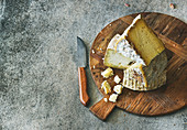 Cheese platter with cheese assortment on wooden board over grey concrete background