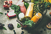 Colorful smoothies in bottles with fresh tropical fruit and greens in basket on grey concrete background