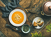 Flat-lay of fall warming pumpkin cream soup with croutons and seeds on board over rustic wooden background