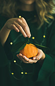 Fresh raw tangerine citrus fruit with leaves in hands of blonde girl wearing green dress with holiday lights bokeh