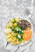 Buddha-Bowl mit Hirse, Kohl, Linsen, Feta, Kartoffeln, Karotten und Sonnenblumenkernen