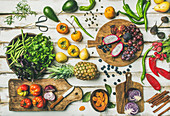 Fresh fruit, vegetables, greens and superfoods on boards over white wooden table