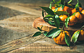 Fresh tangerines with leaves on board over rustic wooden table background