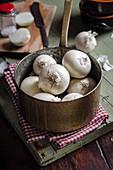 Frische weisse Zwiebeln in Kupfertopf