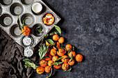Stillleben mit Muffinblech, Papierförmchen und frischen Orangen (Aufsicht)