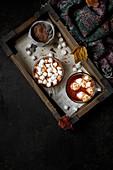 Wintergetränk: Heiße Schokolade mit Marshmallows auf Holztablett (Aufsicht)