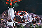 Chocolate bundt cake topped with chocolate ganache, slivered almonds and pomegranate seeds