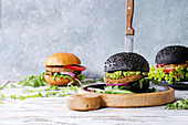 Set of homemade burgers in black and white buns with avocado, tomato sauce, lettuce, arugula, cheese, onion on wood serving board