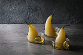 Traditional dessert poached pears in white wine served in glass bowls with syrup and lemon zest