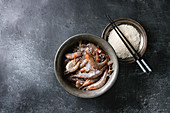 Raw whole fresh uncooked prawns shrimps and plate of raw rice and chopsticks over black texture background