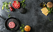 Ingredients for cooking hamburger: Meat beef burger in pan, cheese, ketchup sauce, tomato, black and white buns, arugula salad over dark texture background