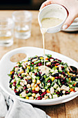 Bohnensalat mit fünf verschiedenen Bohnensorten wird mit Dressing beträufelt