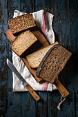 Variety loaves of sliced homemade rye bread whole grain and seeds on wooden cutting board with kitchen towel and knife