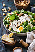 Classic Caesar salad with grilled chicken breast and half of egg in white ceramic plate