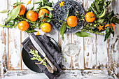 Christmas table decorations with clementines or tangerines with leaves and green branches on black ornate board