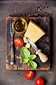 Fresh food ingredients for italian cuisine (Parmigiano, tomato, basil, olive oil) on rustic background