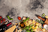 Italian food background with ravioli, vine tomatoes, basil, spaghetti, spinach, onion, parmesan, olive oil, garlic, peppercorns, rosemary and wine