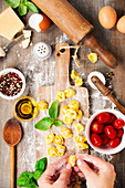 Raw italian pasta tortellini with ingredients on wooden board